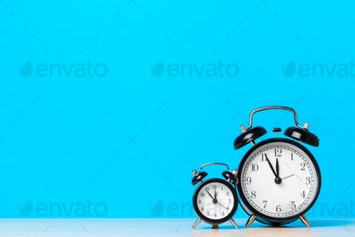Different alarm clocks on table. Time change concept