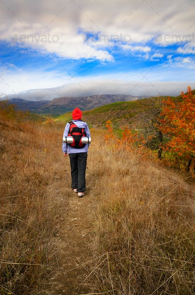 Middle aged active caucasian female model with backpack walk in mountains autumn time
