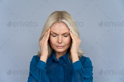 Stressed middle aged lady suffering from headache or migraine, close up view.