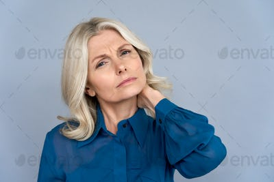 Tired sick middle aged business woman touching neck feeling neck pain.