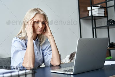 Stressed old business woman suffering from headache after computer work.