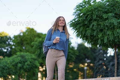 Woman in motion with coffee outdoors