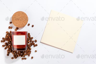 Aroma candle in a glass cup with coffee aroma and post card on white