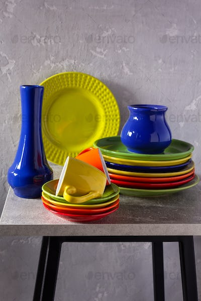 Empty colorful crockery or ceramic dishes set. White kitchen dishware and tableware on wooden table
