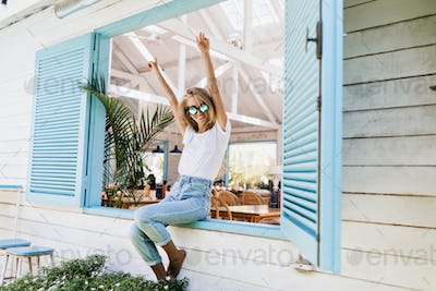 Elegant barefooted girl sitting on window sill and waving hands. Photo of pleased blonde woman in j