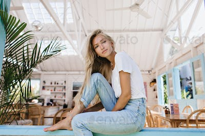 Gorgeous young woman with light hair posing in cafeteria. Portrait of refined female model in blue