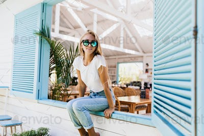 Interested woman in stylish sparkle sunglasses sitting on window sill. Photo of gorgeous blonde fem