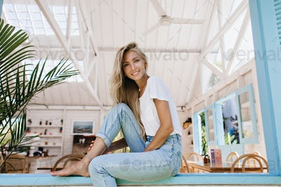 Winsome woman with gently smile sitting on window sill in morning. Interested blonde girl in vintag