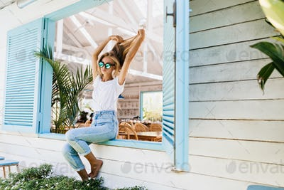 Tanned barefooted woman in vintage jeans playing with her beautiful long hair. Photo of fashionable