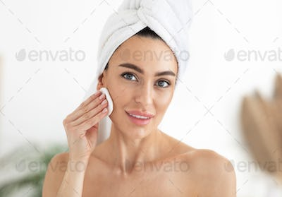 Make up remover. Woman with sponge and micellar water. Skin care and beauty