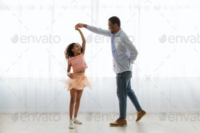 Black father and daughter dancing at home, full length shot