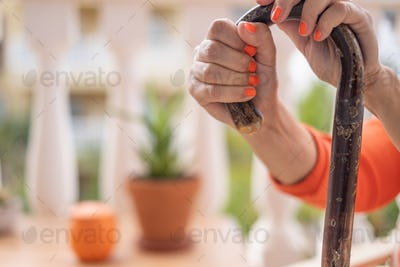 Close-up view of elderly human hands leaning on a walking cane. Senior woman with orange nail polish