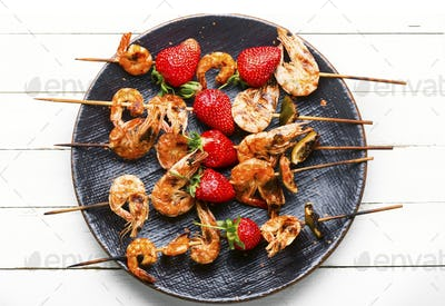 Delicious roasted prawns on a skewer with strawberries