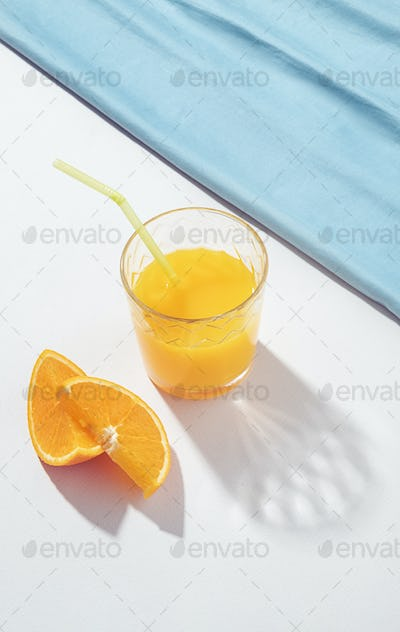 Orange juice and two parts of an orange in the sun