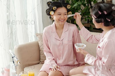 Women applying cleansing clay mask