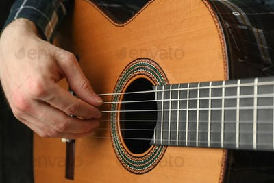 Man playing on classic guitar against dark background, space for text