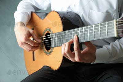 Man playing on classic guitar against light background, space for text