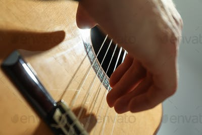 Man playing on classic guitar against light background, closeup