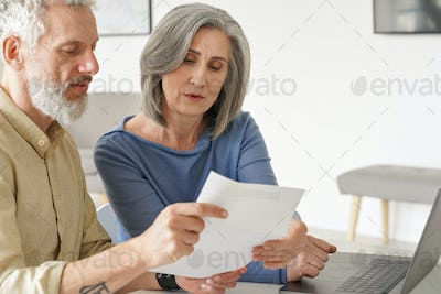 Older mature couple checking bank documents or bills using laptop at home.