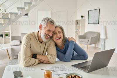 Happy mature older couple laughing, bonding sitting at home table with laptop.