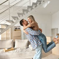 Happy young couple first time home owners hugging in living room on moving day.