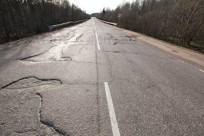 Bad quality road with potholes. Hole in asphalt. Pit, unsafe, hole road. Transportation
