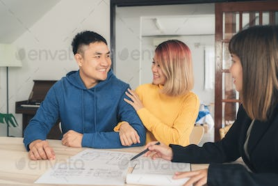 Happy young Asian couple and realtor agent.