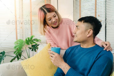 Attractive Asian sweet couple enjoy love moment drinking warm cup of coffee or tea.