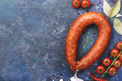 Smoked sausage circle on blue kitchen table with spices, tomatoes and garlic, natural  meat product