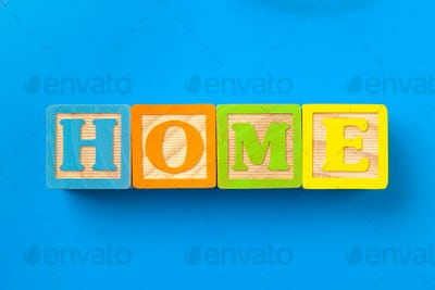 Home. Wooden colorful alphabet blocks on blue background, flat lay, top view