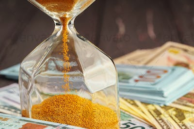 Time and money business concept. Sandglass and money