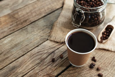 Paper cup of coffee, dry coffee beans in glass jar and spoon at wooden table