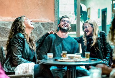 Young friends having genuine fun drinking on happy hour at street bar