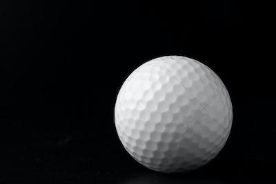 Golf ball close up on black background