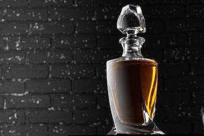 Whisky bottle close up against black grunge wall