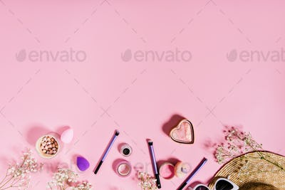 Blush, lilac makeup brushes and straw hat are located on isolated pink background.