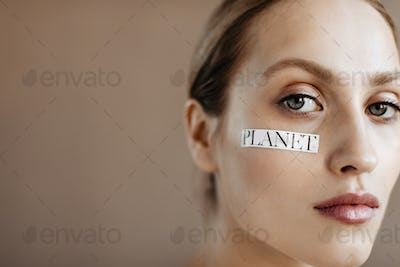 Woman with gray eyes and word planet looking into camera on isolated background