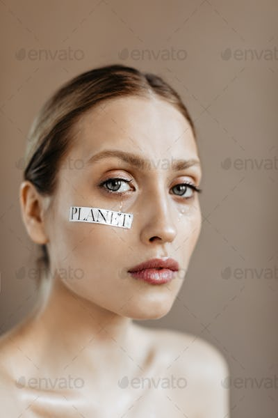Saddened woman with word planet on her cheek posing on beige background. Girl with gray eyes is cry