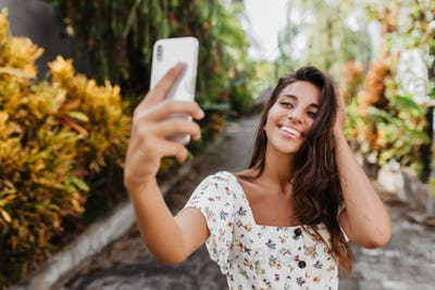 Young beautiful woman in white summer blouse with smile poses for selfie in garden