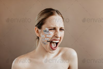 Young woman with white stickers on her face screams violently on beige background