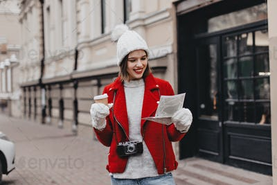 Lovely girl in knitted hat and mittens examines map of sights. Woman in red coat holding cardboard