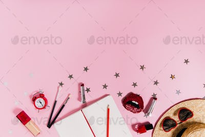 Set of women's makeup accessories and notebook are on pink star background.