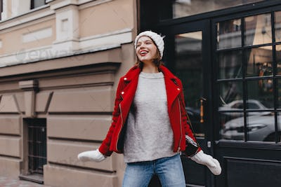 Nice girl in jeans, gray sweater, red coat and knitted hat with mittens posing with smile on street