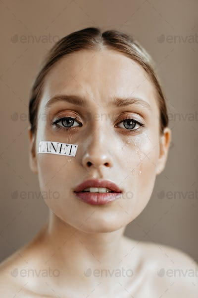 Blue-eyed girl without makeup with word planet written on her cheek with tears looks into camera