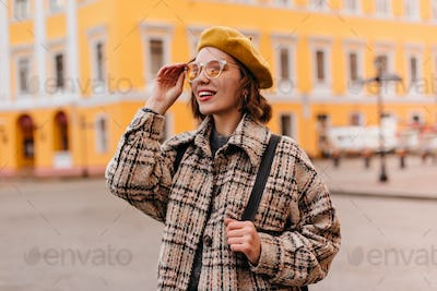 Close-up portrait of young girl in sunglasses admiring cityscape. Woman with curly short hair in be