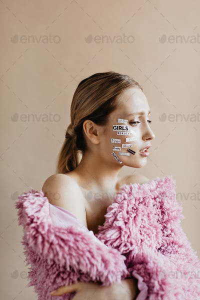 Sad woman with ponytail wrapped in lilac blanket. Shot of girl with stickers on her face posing on
