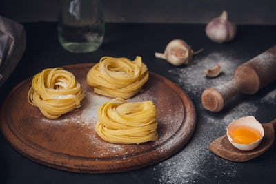 Raw homemade pasta with flour and spices on the rustic background.