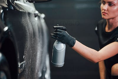 Spraying the vehicle. Modern black automobile get cleaned by woman inside of car wash station