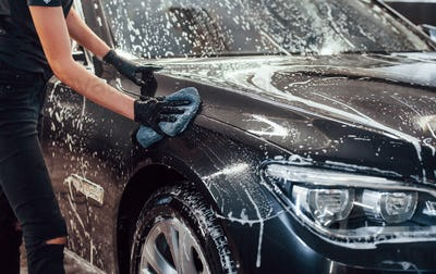 Modern black automobile get cleaned by woman inside of car wash station