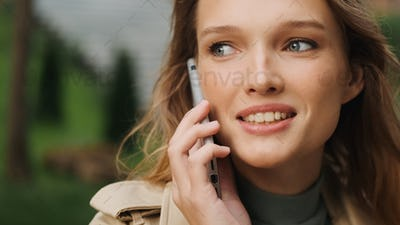 Close up beautiful student girl talking with best friend on phon